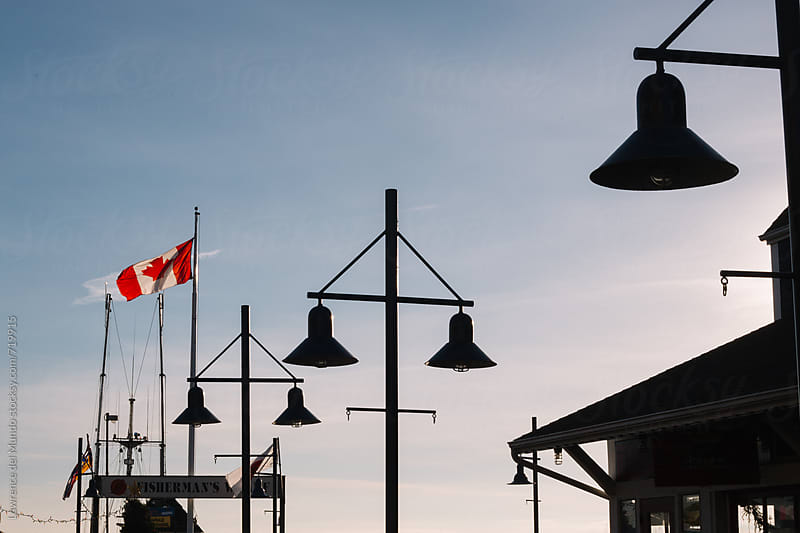 Canadian flag and street lamps over at Fisherman's Wharf by Lawrence del Mundo for Stocksy United