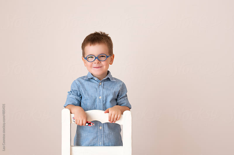 Portrait of an adorable boy smiling, against a beige background kneeling on a white chair. by Lea Csontos for Stocksy United