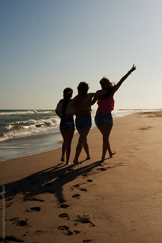 Three unrecognizable friends walking along summer beach by Guille Faingold for Stocksy United