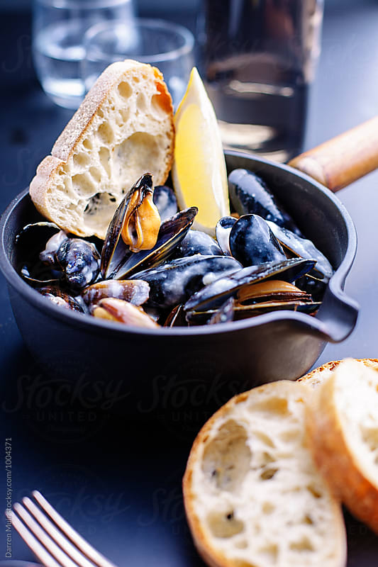 Mussels in a white wine cream sauce. by Darren Muir for Stocksy United