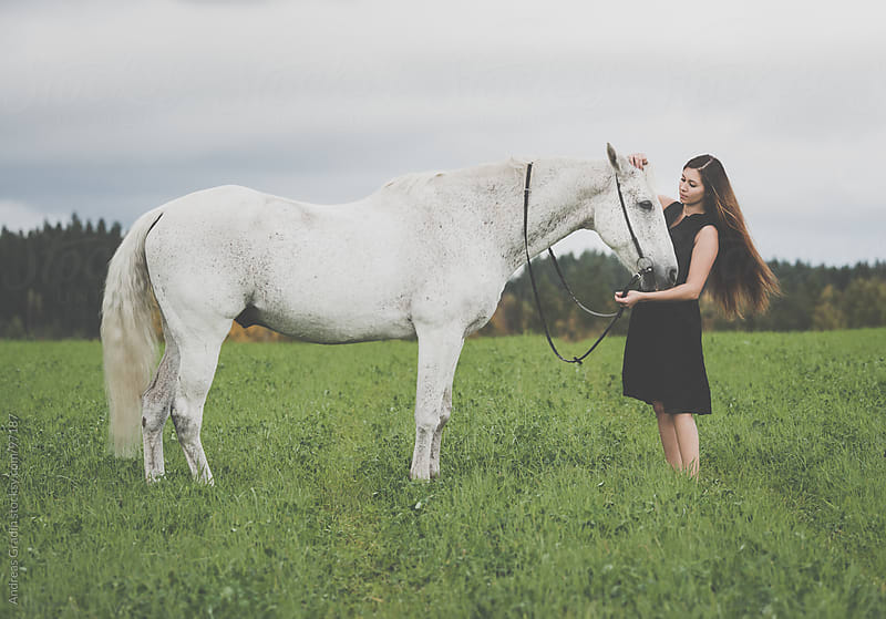 girl and a white horse  by Andreas Gradin for Stocksy United