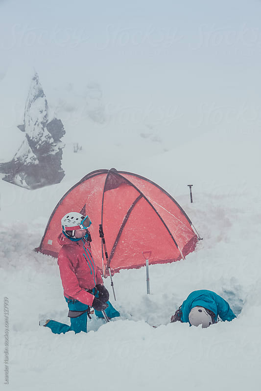 freeskier building up an igloo as emergency accommodation by Leander Nardin for Stocksy United