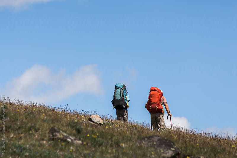Two hiking companions backpacking and exploring remote alpine wilderness area by Matthew Spaulding for Stocksy United