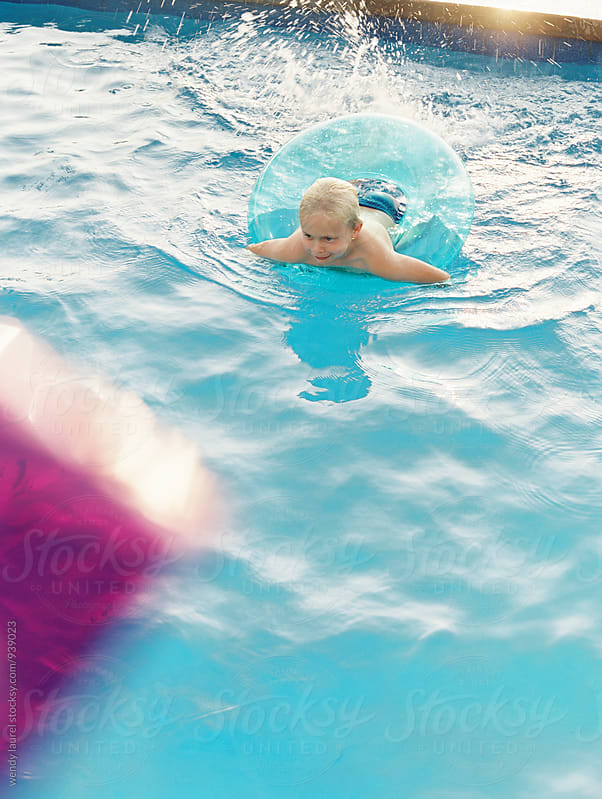 little boy into intertube floaty in pool with sun and pink by wendy laurel for Stocksy United