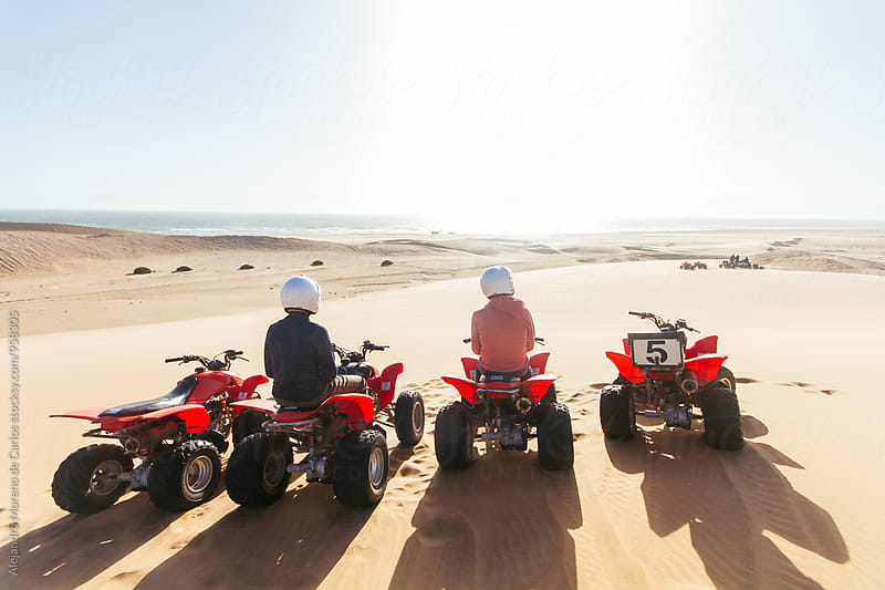Two people sitting on quad bikes and looking at beautiful landscape by Alejandro Moreno de Carlos for Stocksy United