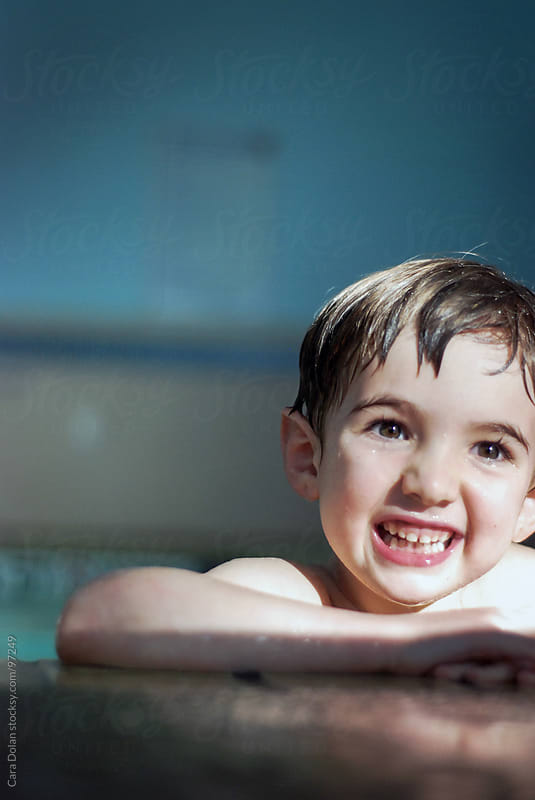 Smiling boy hanging on the edge of an indoor swimming pool by Cara Dolan for Stocksy United