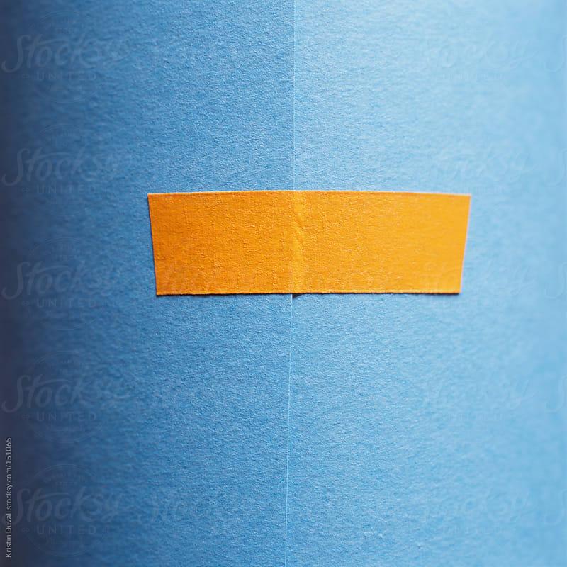 Orange tape on blue paper by Kristin Duvall for Stocksy United