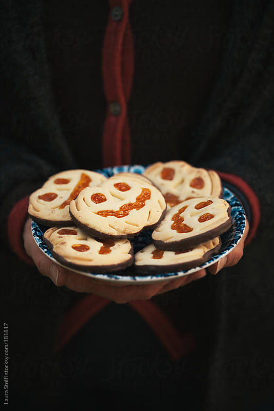 Halloween pumpkin shaped cookies in vintage dish by Laura Stolfi for Stocksy United