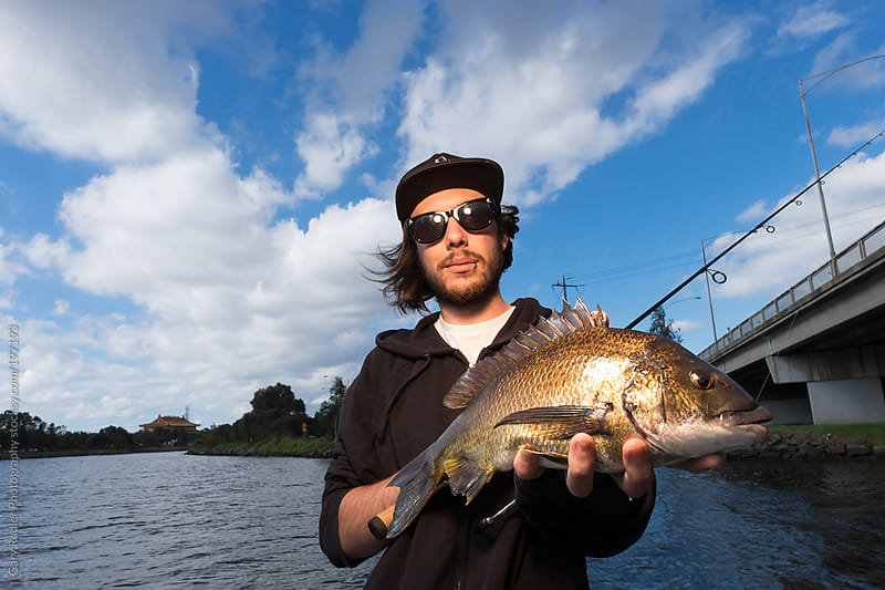 Young adult fisherman holding a bream by Gary Radler Photography for Stocksy United