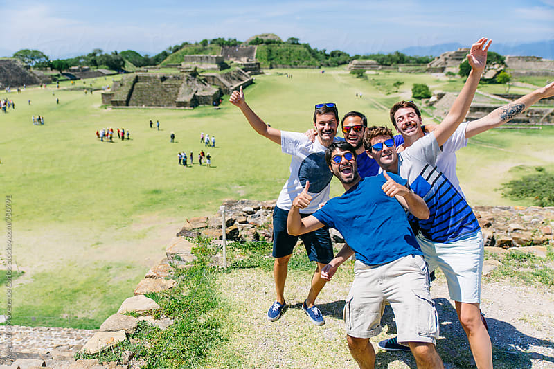 Group of happy friends posing happy for a photo in ancient ruins during their vacation by Alejandro Moreno de Carlos for Stocksy United