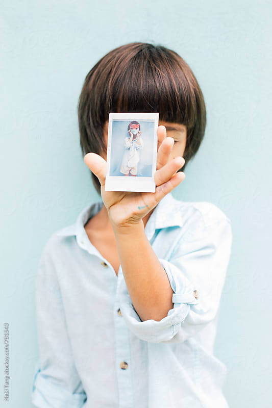 A boy holding polaroid portrait of himself playing with his handmade paper mask by Nabi Tang for Stocksy United