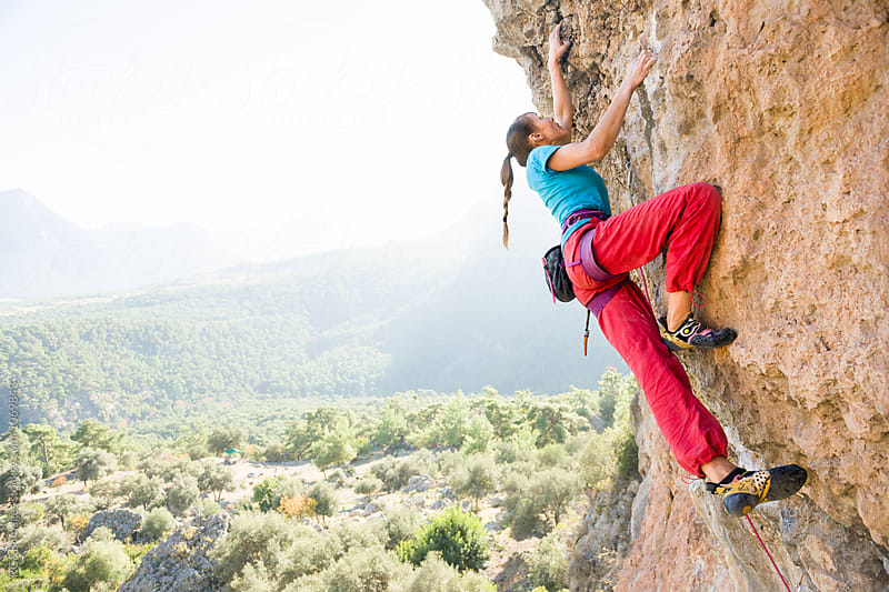 Climber doing a hard move on a rock climbing route by RG&B Images for Stocksy United