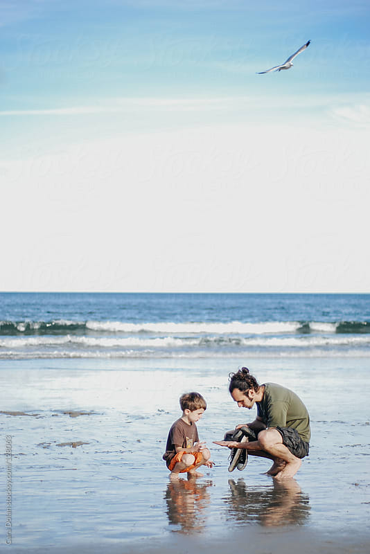 Boy and his dad together on a beach in summer by Cara Dolan for Stocksy United