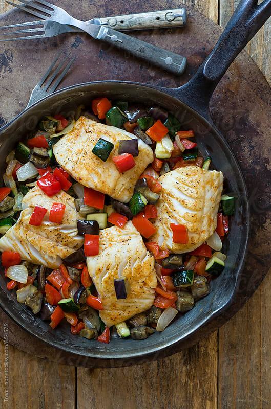 Delicious roasted ratatouille fish with vegetables on frying pan by Trent Lanz for Stocksy United