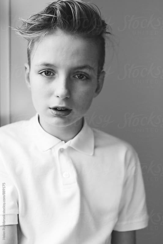 Black and white portrait of a teenage boy by Helen Rushbrook for Stocksy United