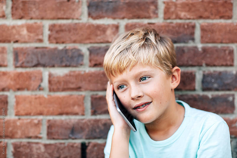 smiling boy talks on a phone by Kelly Knox for Stocksy United