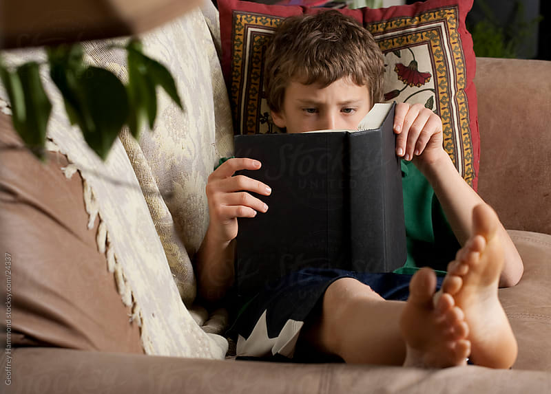 Boy on Couch Reading a Book by Geoffrey Hammond for Stocksy United