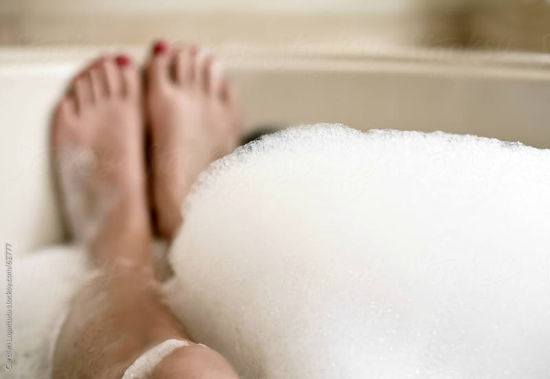 Womans's legs - downtime in the bubble bath by Carolyn Lagattuta for Stocksy United
