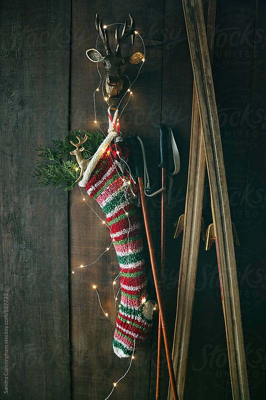 Striped wool stocking with old skis and sparkling lights by Sandra Cunningham for Stocksy United
