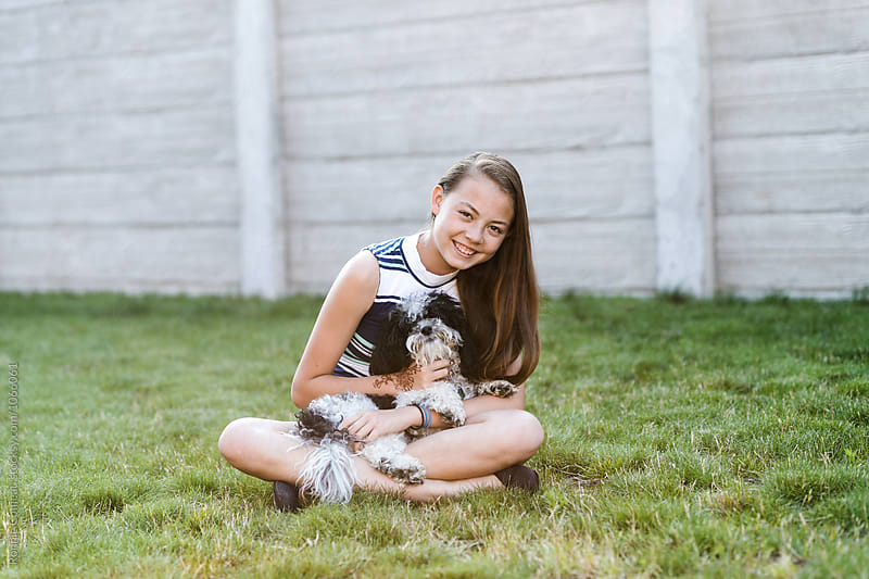 Smiling Teen Holding Her Puppy by Ronnie Comeau for Stocksy United