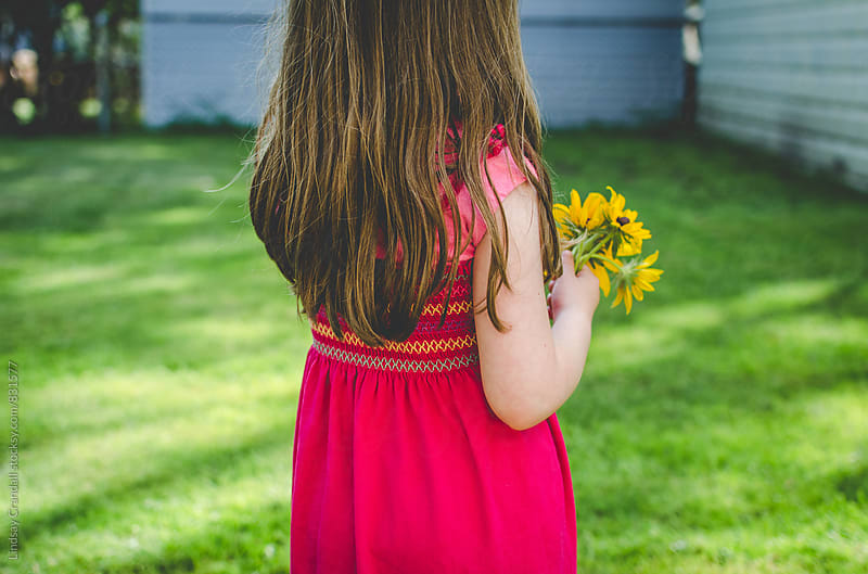 Back of child holding small bouquet of flowers by Lindsay Crandall for Stocksy United