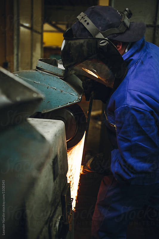 detail of a metal worker with protection mask grinding metal plate in a workshop