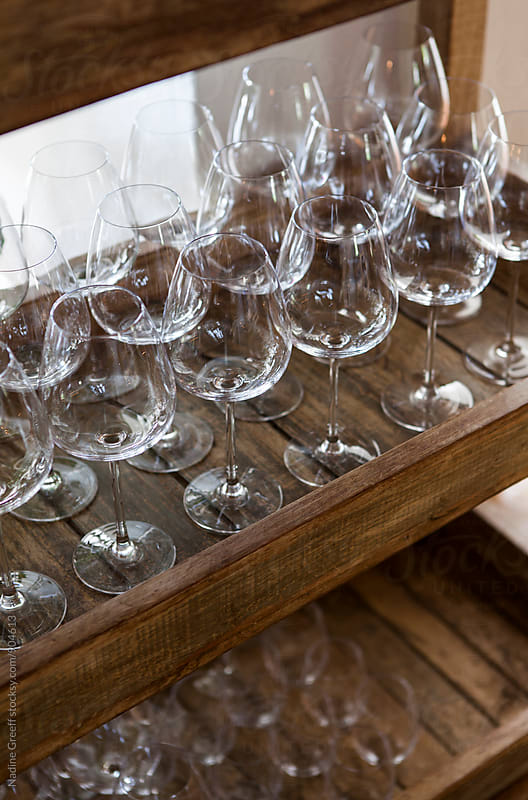 Empty wine glasses on a trolley in a cafe by Nadine Greeff for Stocksy United