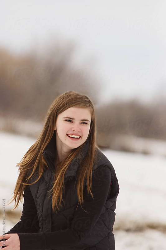 Teen smiling while preparing to throw snowballs by Tana Teel for Stocksy United