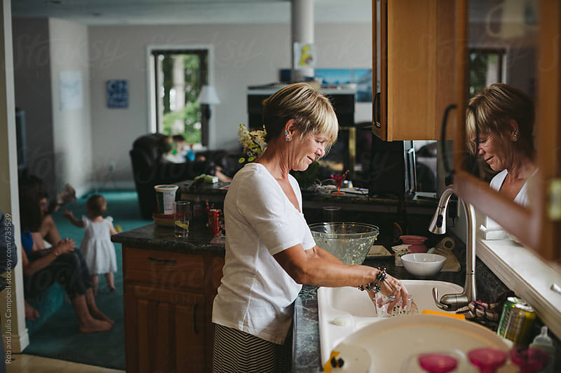 Mature woman smiling doing the dishes by Rob and Julia Campbell for Stocksy United