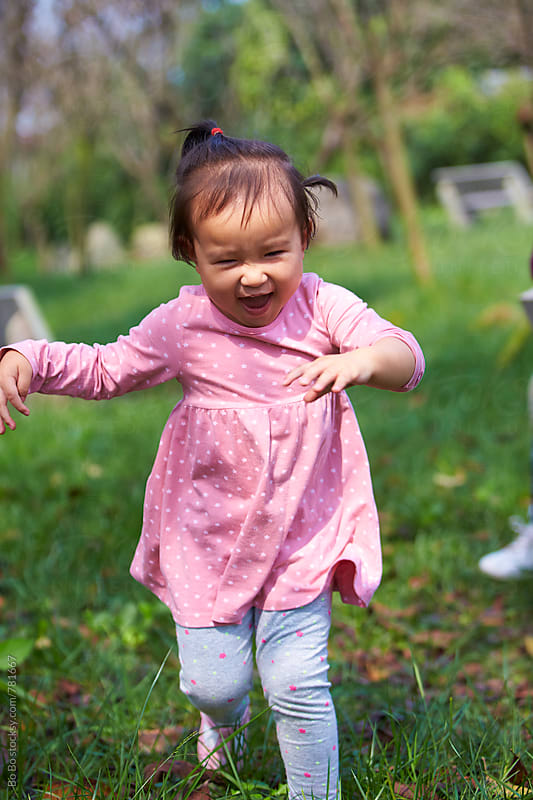 happy little asian girl running outdoor in the woods by Bo Bo for Stocksy United