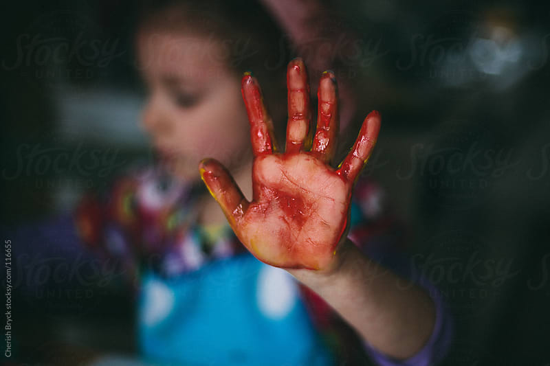 Little girl paints her hand red. by Cherish Bryck for Stocksy United