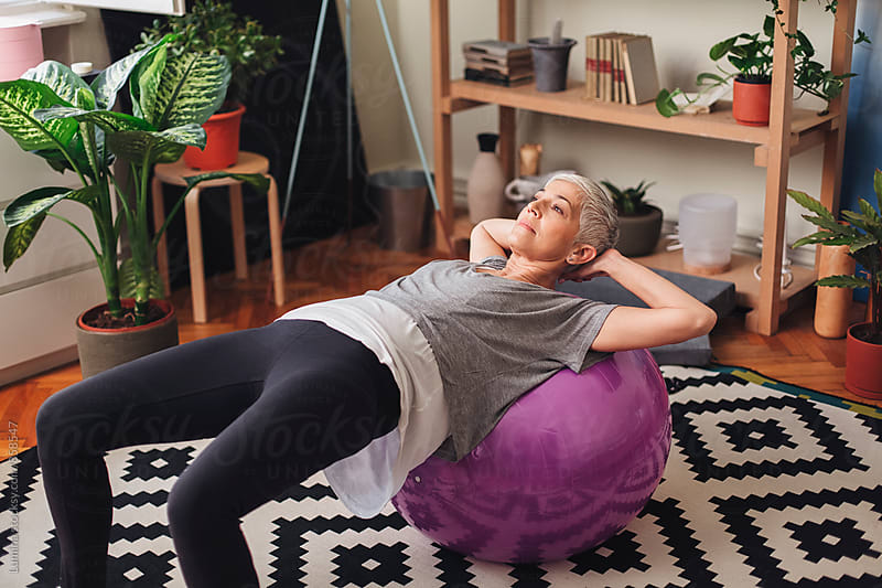 Woman exercising with a fitness ball at Home by Lumina for Stocksy United