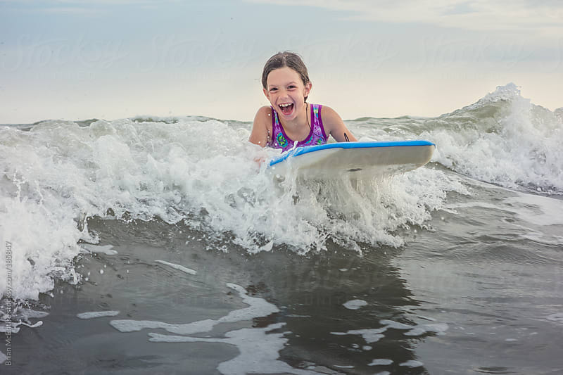 Girl Ecstatic about Catching a Wave while Body Boarding  by Brian McEntire for Stocksy United