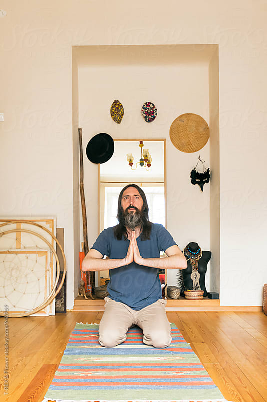Bearded man in Namaste sitting on floor by Danil Nevsky for Stocksy United