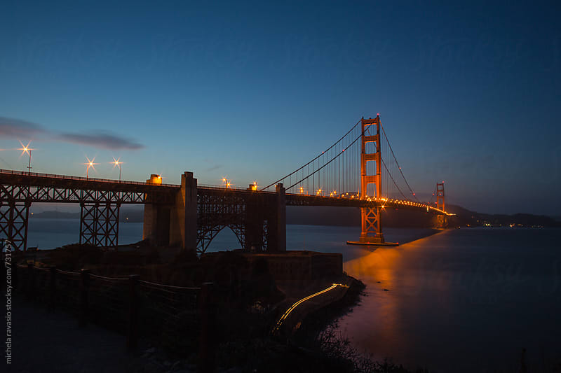 The Golden Gate Bridge after sunset with the light stripes of a car by michela ravasio for Stocksy United