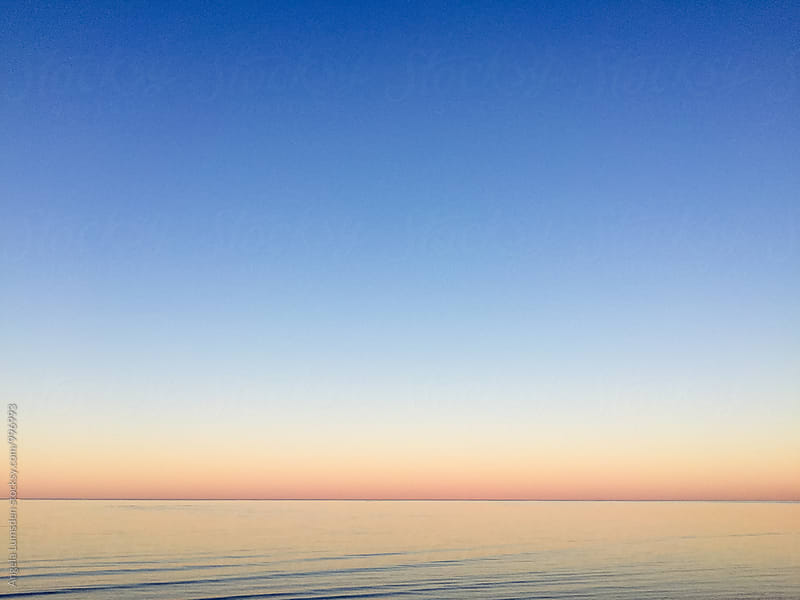Color gradient in the sky over calm water at sunset by Angela Lumsden for Stocksy United