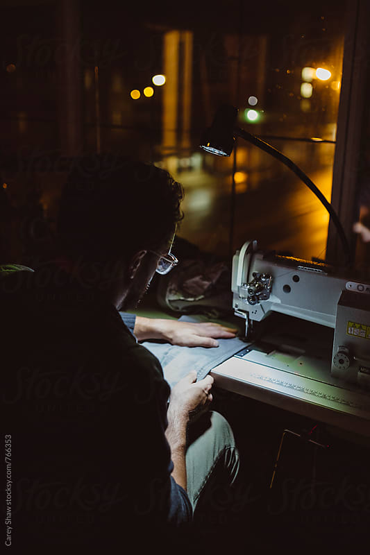 Evening portrait of male sewing in workshop by Carey Shaw for Stocksy United