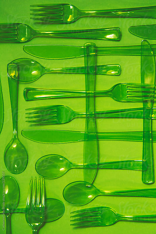 Green plastic cutlery on a green background... by Catherine MacBride for Stocksy United