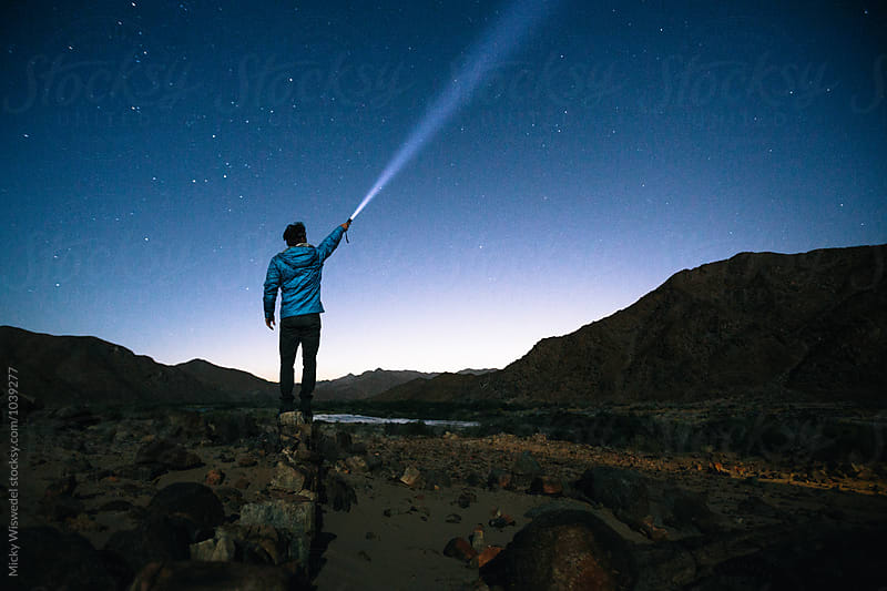 Hiker standing outdoors shining a torch beam into the stars by Micky Wiswedel for Stocksy United