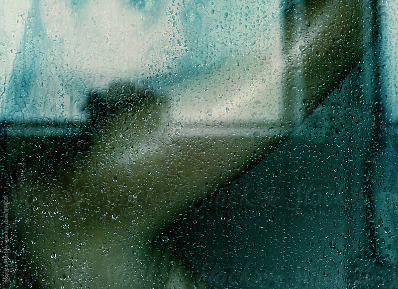 Woman in hot shower, arm raised, looking out through wet glass by Monica Murphy for Stocksy United