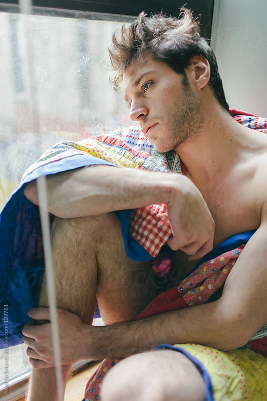 Young Man Waking Up in the Morning Sitting by Window with Quilt by Joselito Briones for Stocksy United