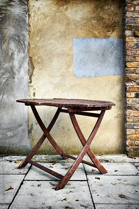 A wooden table by a wall by James Ross for Stocksy United