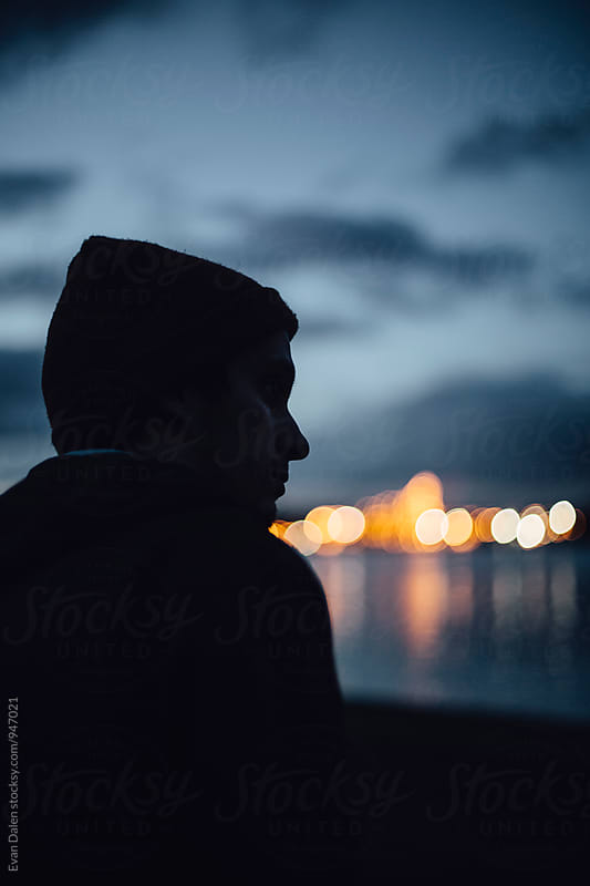 Man Sitting by River at Dusk by Evan Dalen for Stocksy United