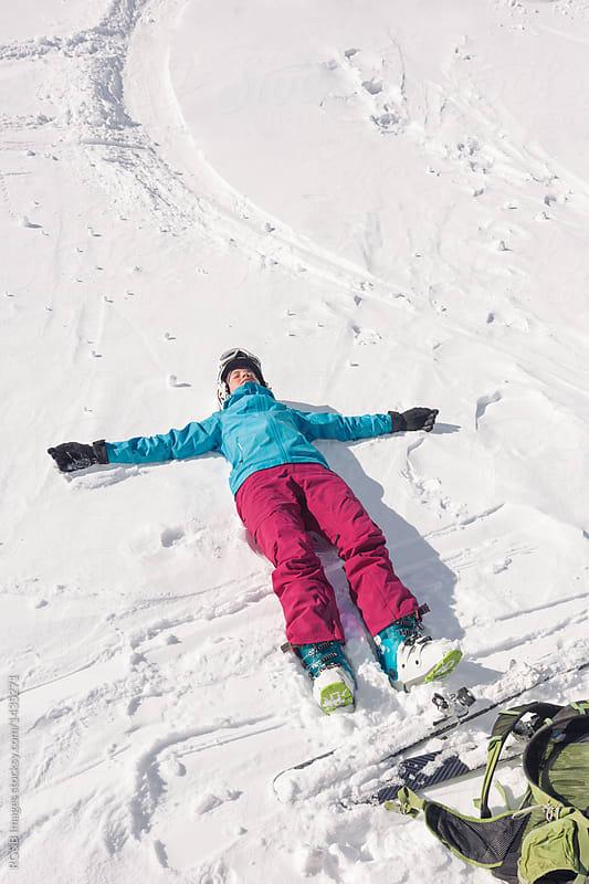 Woman wearing ski equipment lying down in the snow