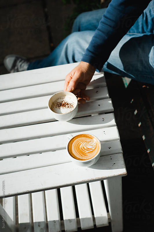 Man sitting at a table holding a cup of coffee by Suzi Marshall for Stocksy United
