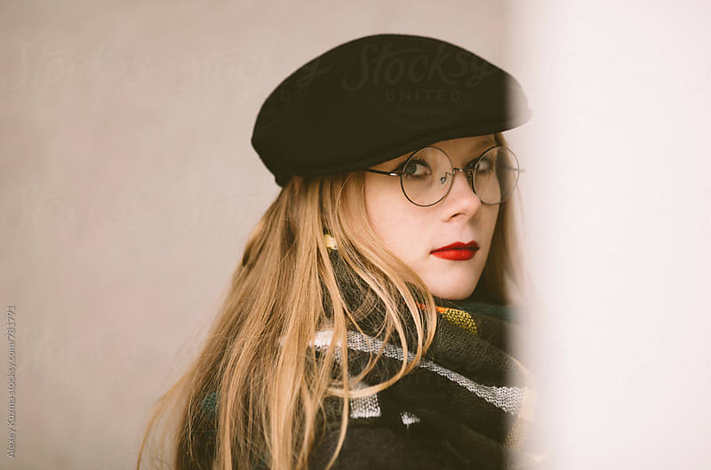 young woman with black hat and round glasses on the street by Alexey Kuzma for Stocksy United