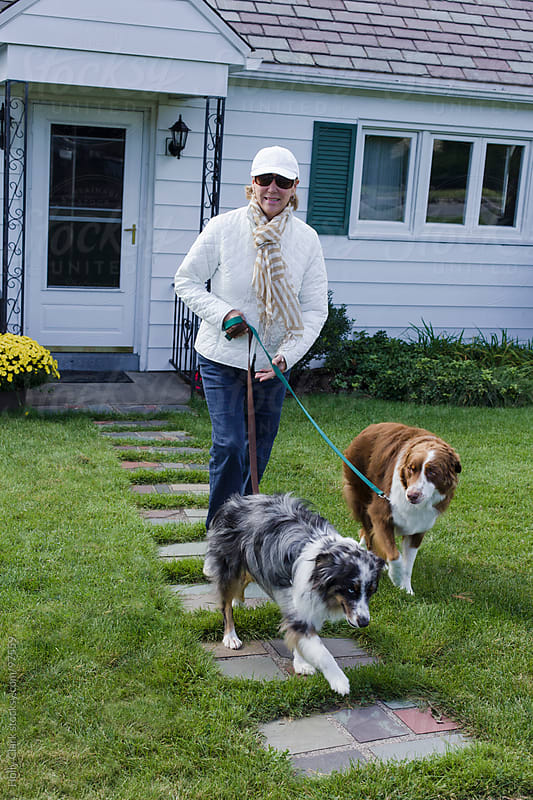 A woman walks her dogs down the front walkway to her house. by Holly Clark for Stocksy United