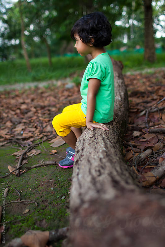 Little girl sitting on a tree trunk in a forest in a contemplative mood by Saptak Ganguly for Stocksy United