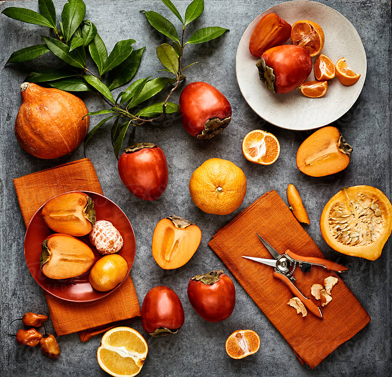 Still life of various orange colored fruits and vegetables on concrete by Trinette Reed for Stocksy United