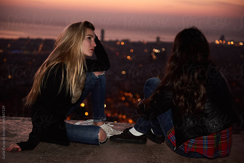 Close-up of two young women against of evening cityscape by Guille Faingold for Stocksy United